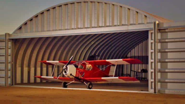 Яростный самолет вырывается из бескаркасного арочного ангара флексить